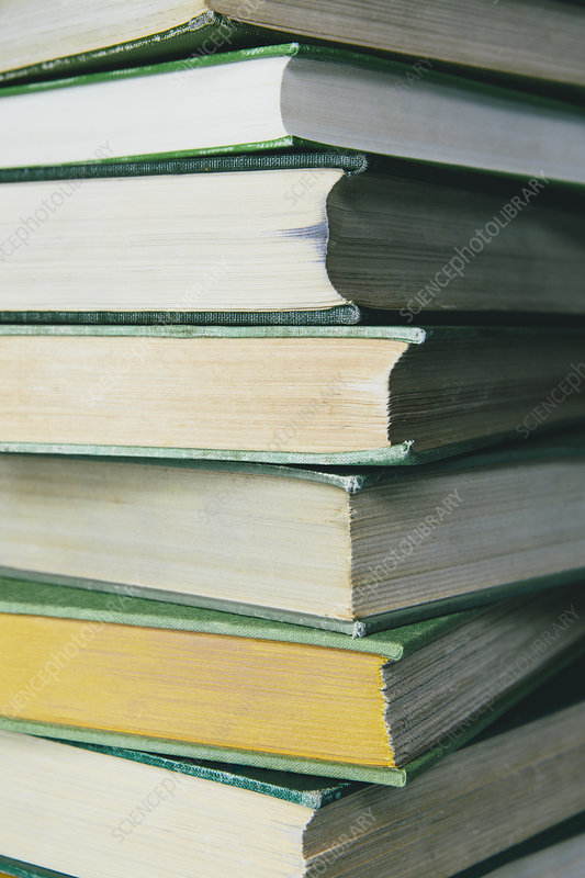 A stack of old books yellowed with age