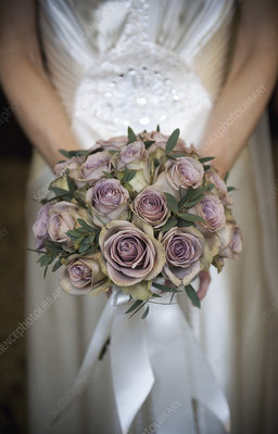 A bride in a white dress with bouquet