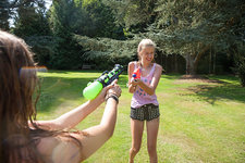 Teenage girls firing water guns in garden