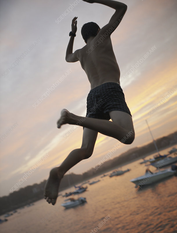 A boy leaping off a dock