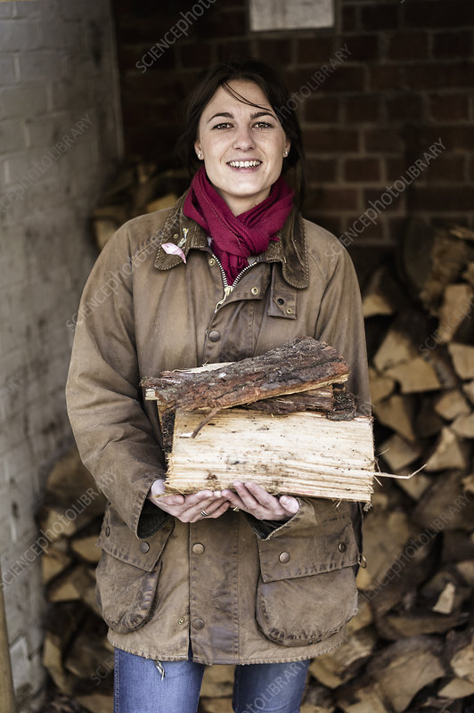 Woman carrying split logs for firewood