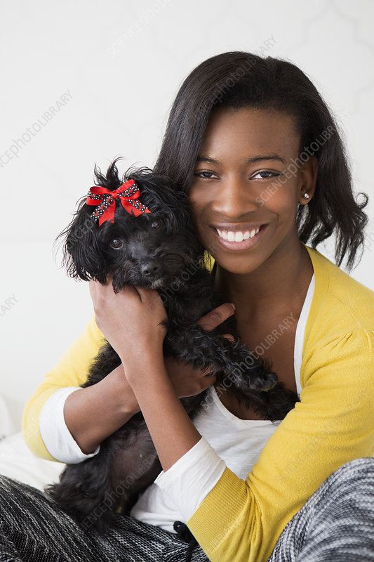 Young girl smiling, holding a pet dog