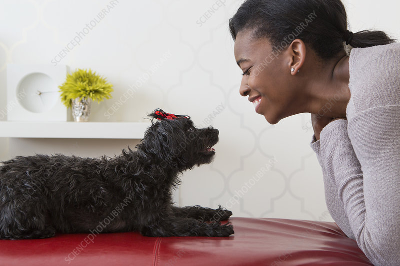 Young girl playing with a black pet dog