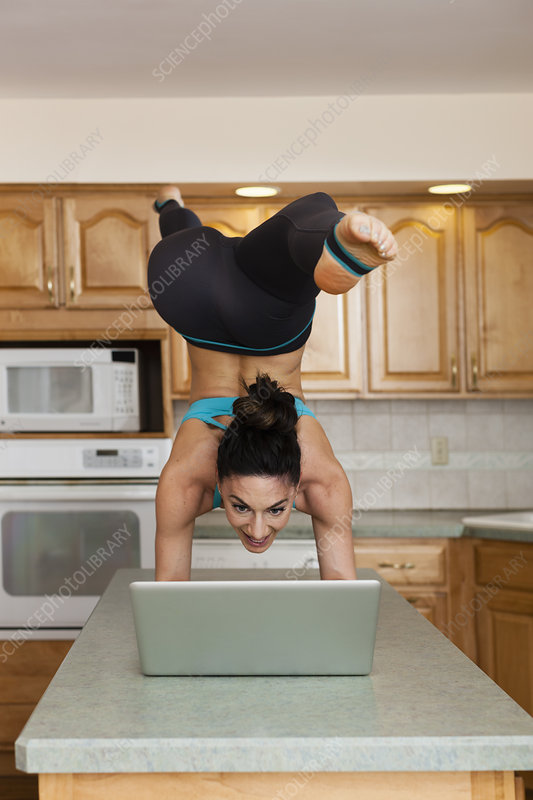 Woman doing handstand in a kitchen