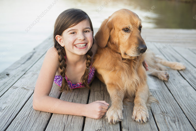 Young girl and a dog lying on a jetty