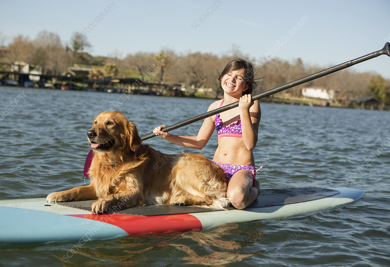 Child and a dog on a paddleboard