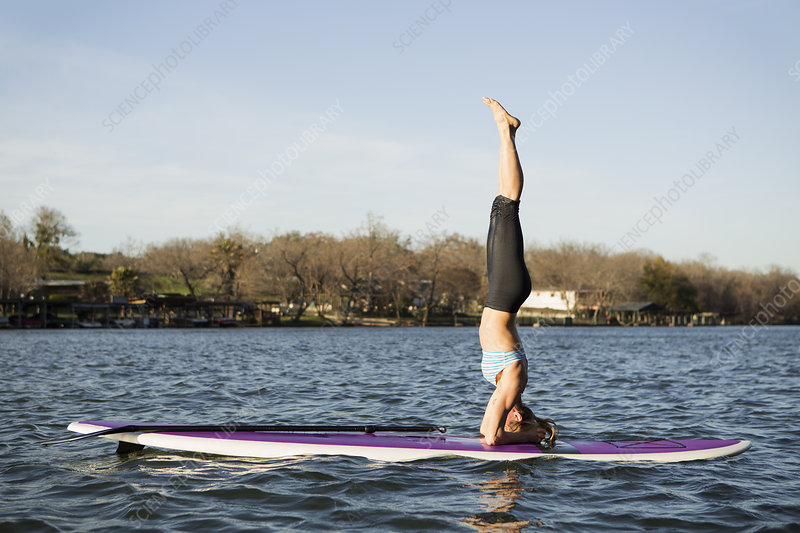 Woman doing headstand on paddle board