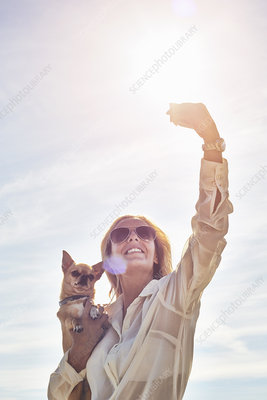 Woman photographing herself with dog