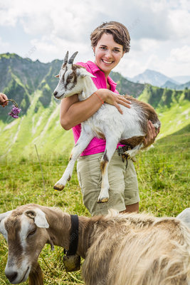 Young woman holding kid goat