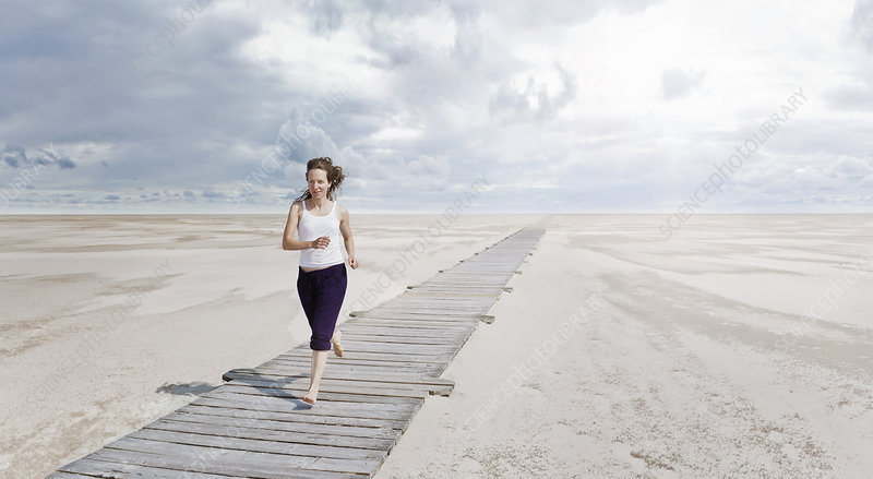 Woman running on boardwalk