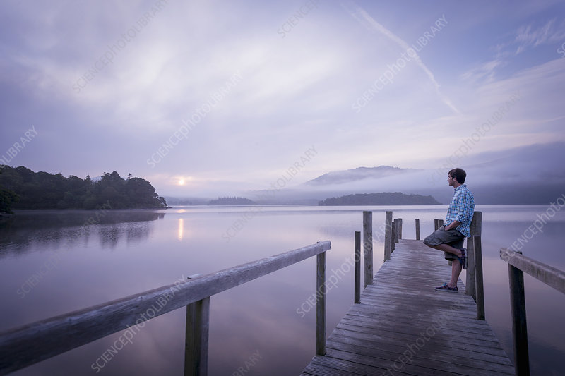 Man on pier by tranquil lake, Cumbria, UK