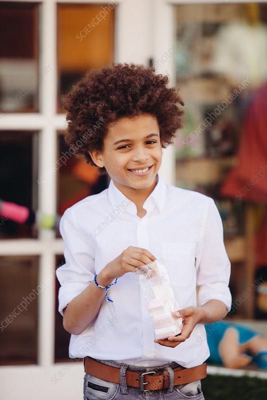 Boy eating confectionary outside shop