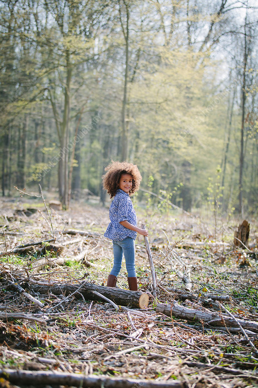 Portrait of girl in woods with stick