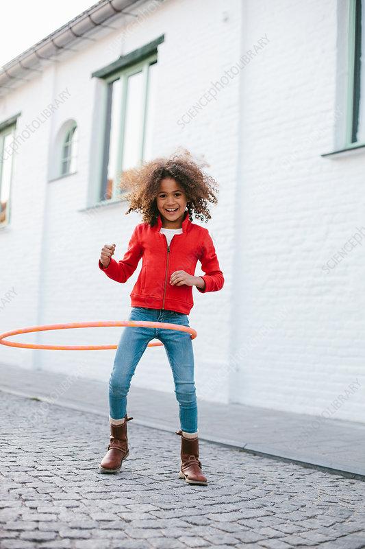 Young girl practicing with hoola hoop