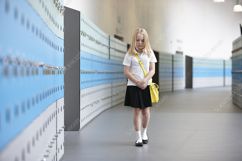 Unhappy schoolgirl walking alone