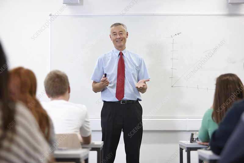 Mature male teacher in front of class