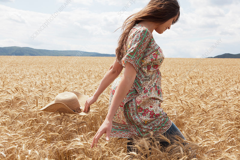 Woman walking through wheat field