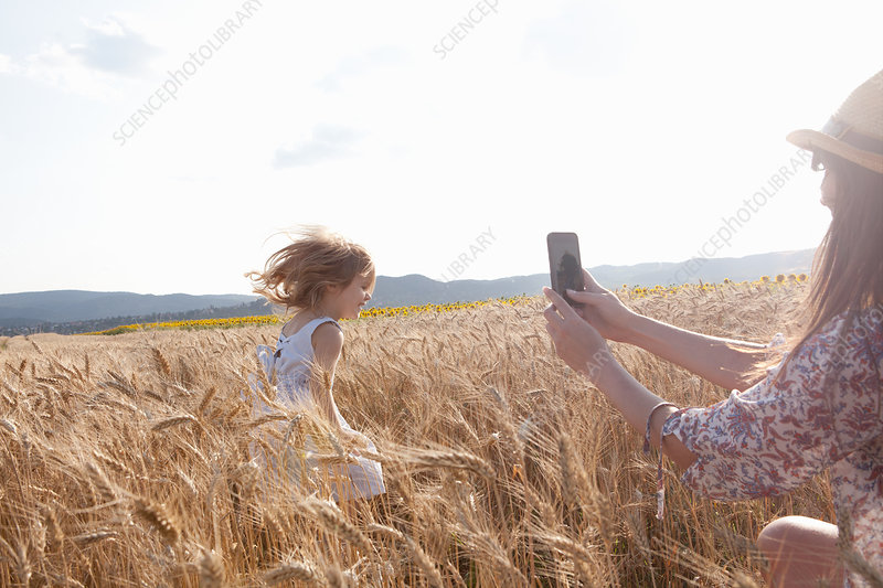 Mother photographing girl
