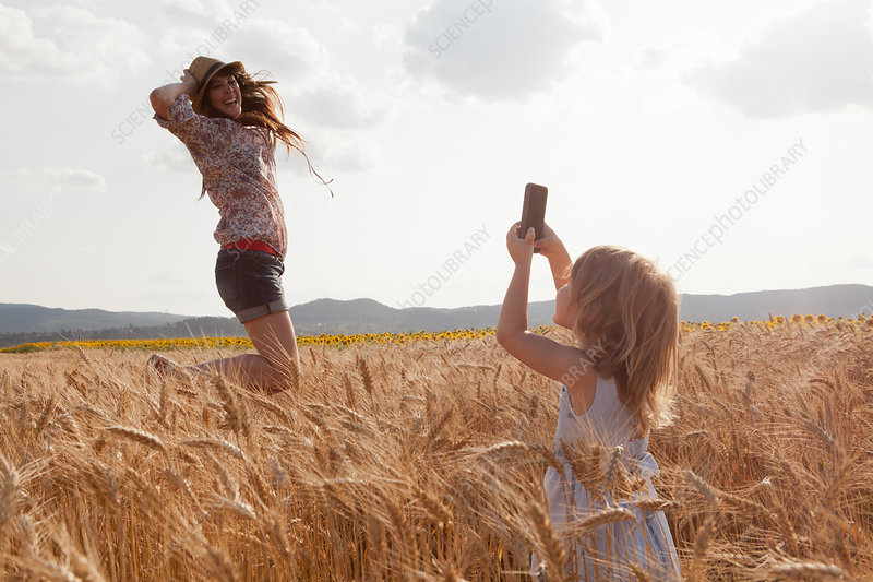 Girl taking photograph of mother
