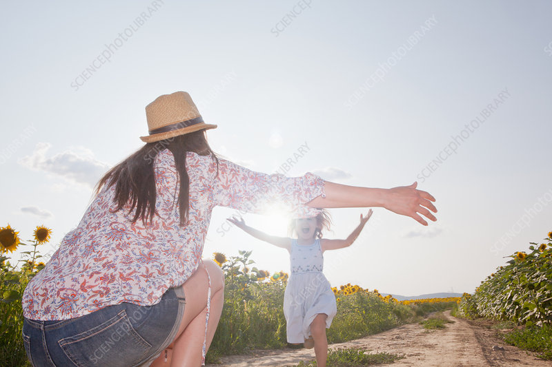 Girl running through field to mother