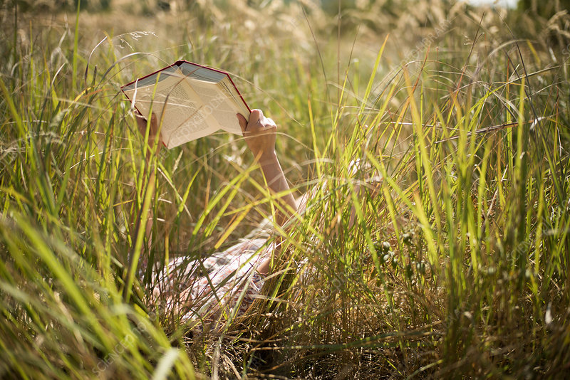 Woman lying in long grass reading book