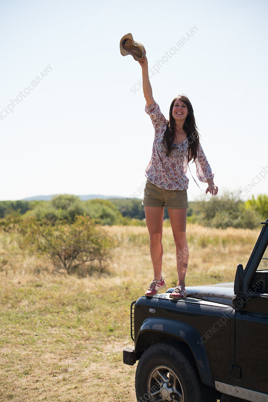 Women standing on hood of car waving hat