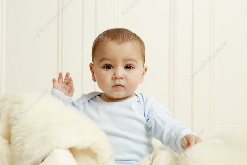 Baby sitting on sheepskin rug
