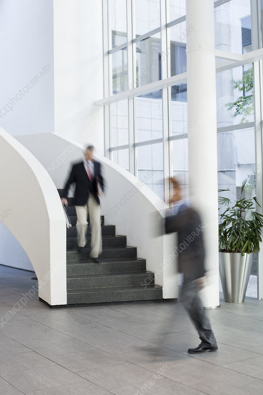 Businessmen on the move in office atrium
