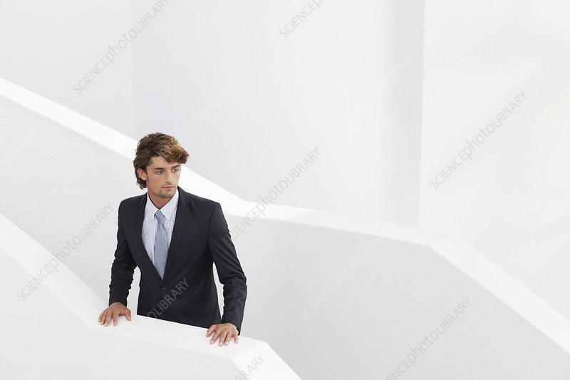 Young businessman waiting on stairs