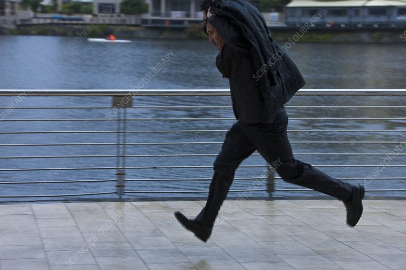 Businessman running to shelter from rain