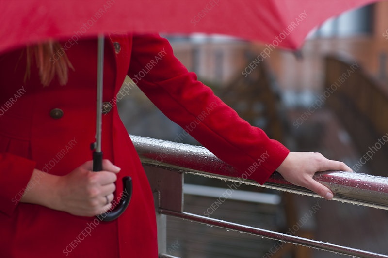 Woman in red carrying umbrella