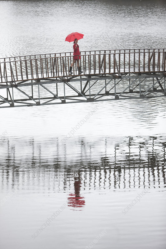 Woman in red crossing footbridge in rain