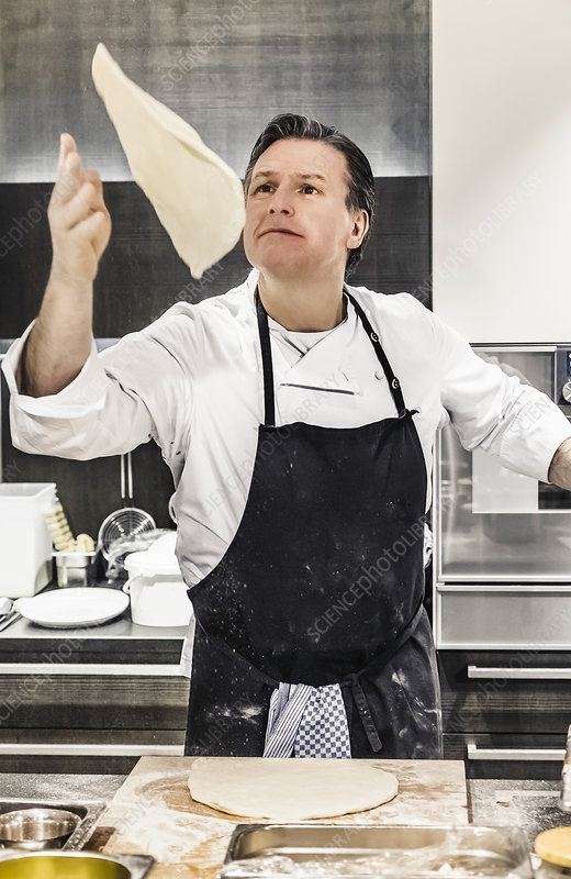 Chef throwing pizza dough mid air