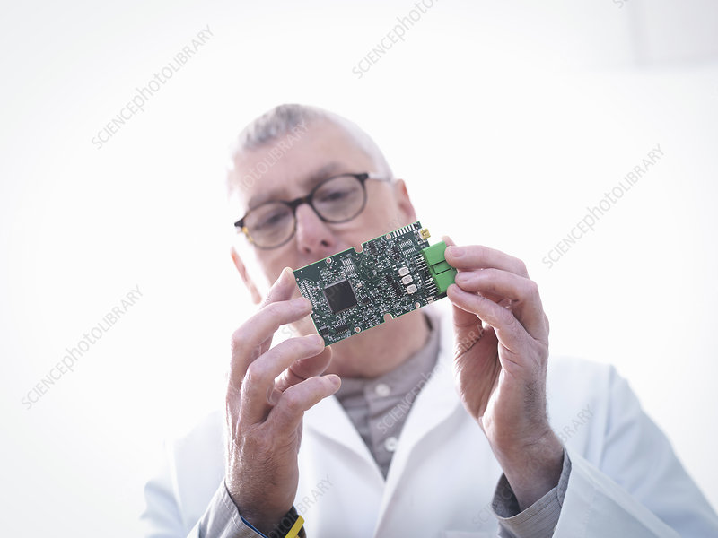 Engineer inspecting electronic circuitry