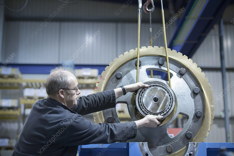 Engineer moving large gear wheel