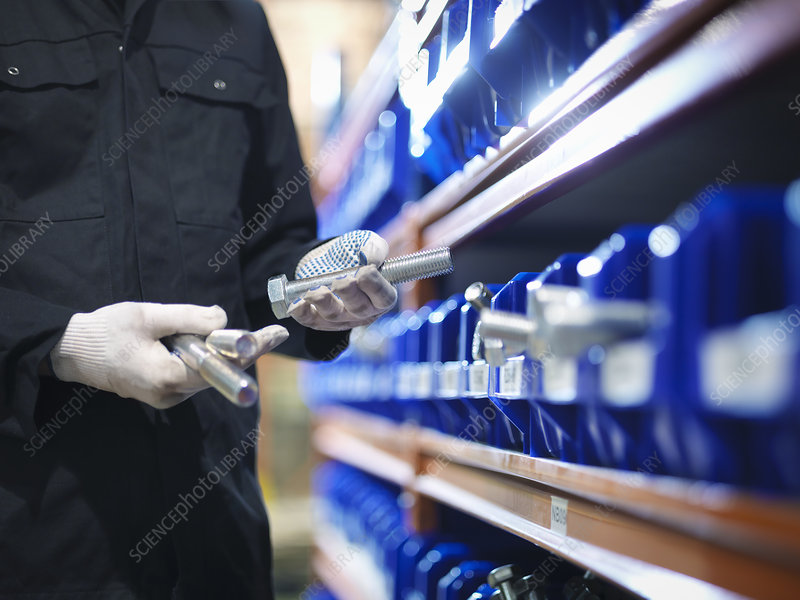Engineer selecting bolts from store