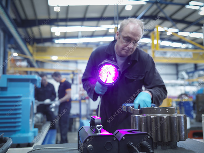 Engineer testing for cracks in gear wheel