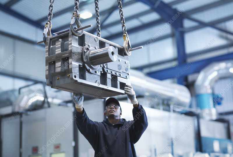 Engineer using crane to move gearbox
