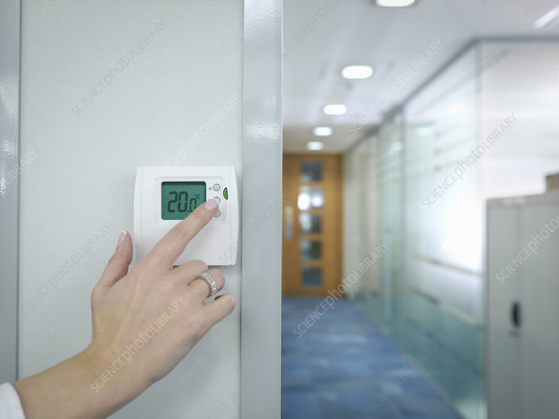Office worker adjusting thermostat