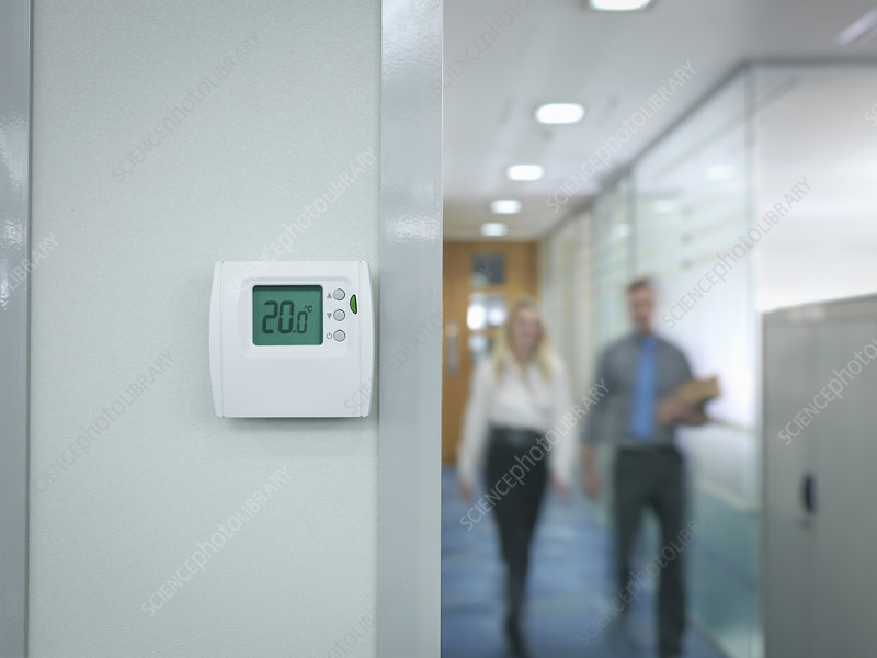 Office workers walking towards thermostat