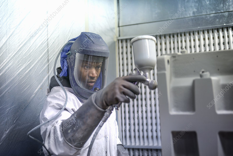 Worker paint spraying gearboxes