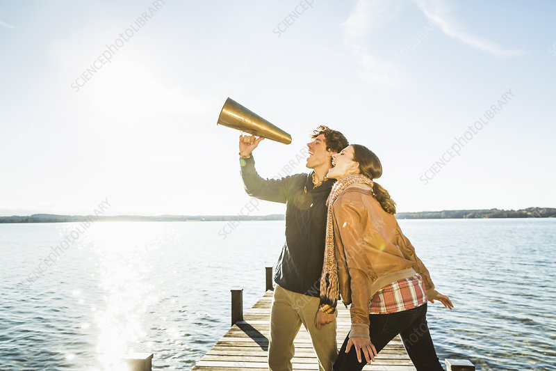 Couple using megaphone by lake