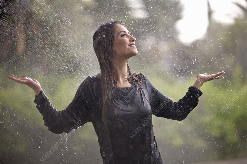 Drenched woman in rainy park