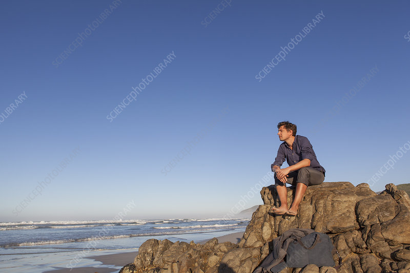 Man sitting on rock at seaside
