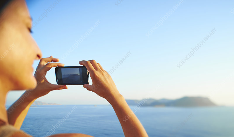 Woman checking photographs on smartphone