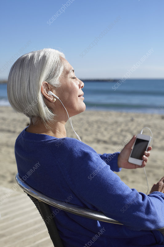 Woman listening to music on beach