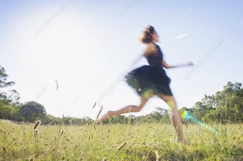 Woman running through summer meadow