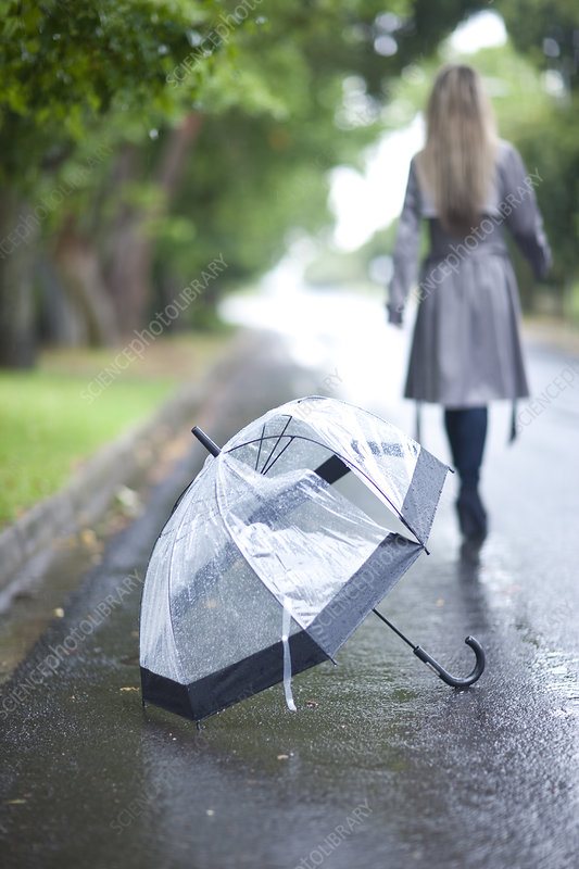 Young woman and broken umbrella in park