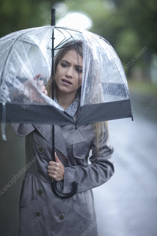 Young woman looking at hole in umbrella