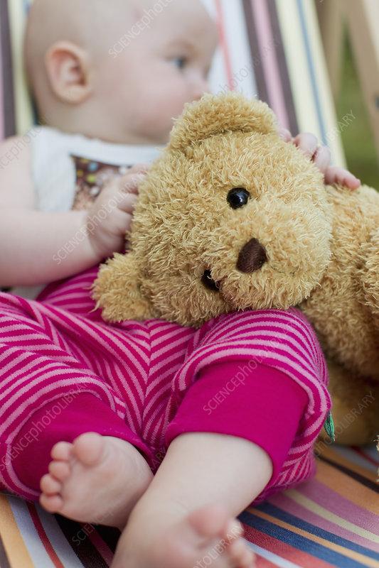 Baby girl holding teddy bear
